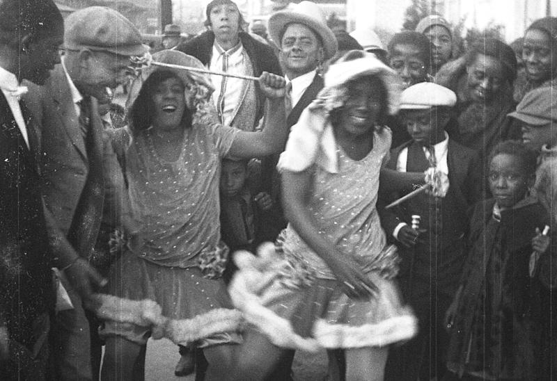 """This still frame from a film strip provided by Story Sloan Gallery shows women dressed as """"baby dolls"""" dancing on a New Orleans street at Mardi Gras in 1931. The first known group of women to strut and dance in short """"baby doll"""" dresses was a group of African-American prostitutes who wanted to outdo another group in 1912, but the style soon spread to respectable black neighborhoods and is seeing a modern revival. (AP Photo/Story Sloan Gallery)"""