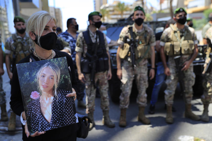 A woman holds a portrait of a victim who killed during the last year's massive blast at Beirut's seaport, protest near the tightly-secured residents of parliament speaker Nabih Berri, in Beirut, Lebanon, Friday, July 9, 2021. The protest came after last week's decision by the judge to pursue senior politicians and former and current security chiefs in the case, and requested permission for their prosecution. (AP Photo/Hussein Malla)