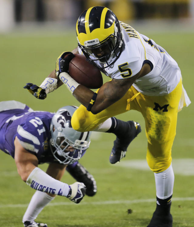 Michigan running back Justice Hayes (5) slips past Kansas State linebacker Jonathan Truman (21) during the first half of the Buffalo Wild Wings Bowl NCAA college football game on Saturday, Dec. 28, 2013, in Tempe. (AP Photo/Matt York)