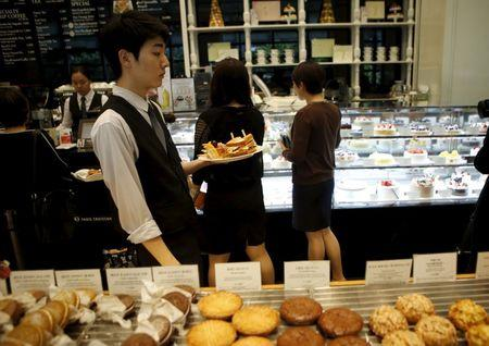 An employee serves sandwiches during lunchtime at a bakery in central Seoul