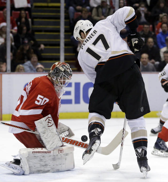 Detroit Red Wings goalie Jonas Gustavsson (50) of Sweden deflects a shot by Anaheim Ducks left wing Dustin Penner (17) during the first period of an NHL hockey game in Detroit, Tuesday, Dec. 17, 2013. (AP Photo/Carlos Osorio)