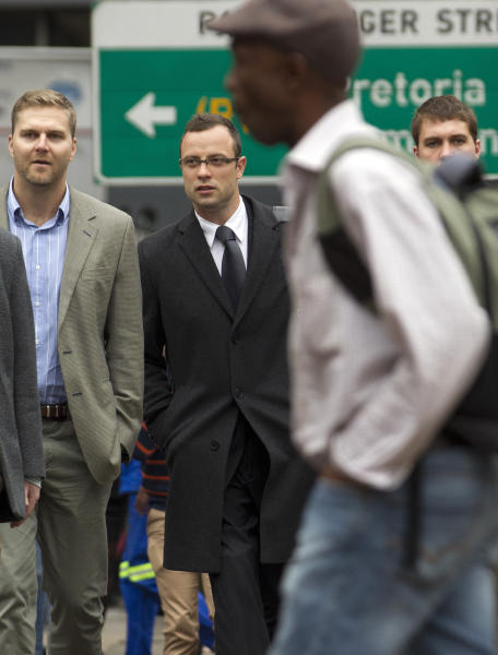 Oscar Pistorius, second from left, accompanied by unidentified men arrives at the high court for his murder trial in Pretoria, South Africa, Tuesday, March 11, 2014. Pistorius is charged with murder for the shooting death of his girlfriend, Reeva Steenkamp, on Valentines Day in 2013. (AP Photo/Themba Hadebe)