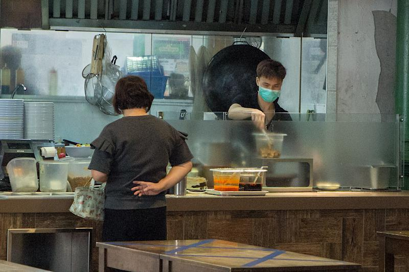 A hawker at Lau Pa Sat prepares a take-away meal for a customer on 7 April 2020, the first day of Singapore's month-long circuit breaker period. (PHOTO: Dhany Osman / Yahoo News Singapore)