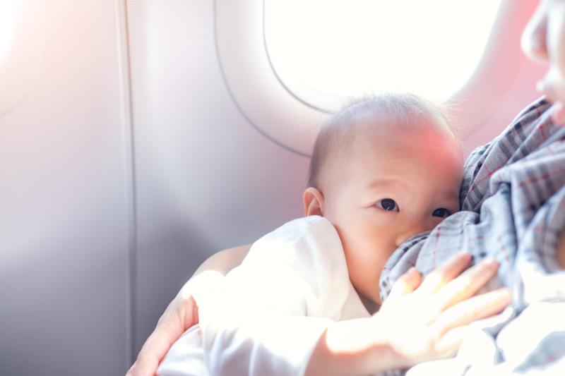 Asian mother is breastfeeding Cute little Asian 18 months toddler baby boy child on Airplane,Toddler lying on mother's laps, BreastFeeding in Public concept, harsh sunlight overexposed at baby hand