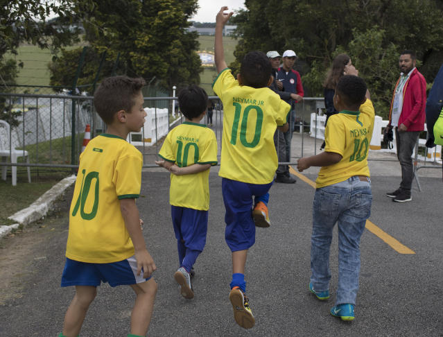 Boys, wearing Brazilian national team Neymar jerseys, celebrate because they were allowed entry at the Granja Comary training center to watch the national soccer team training session, in Teresopolis, Brazil, Friday, May 25, 2018. Neymar, the worlds highest paid soccer player, is nearly recovered from a foot operation and has joined 16 of his teammates in Teresopolis, looking ahead to competing in Russia at the World Cup in July. (AP Photo/Leo Correa)