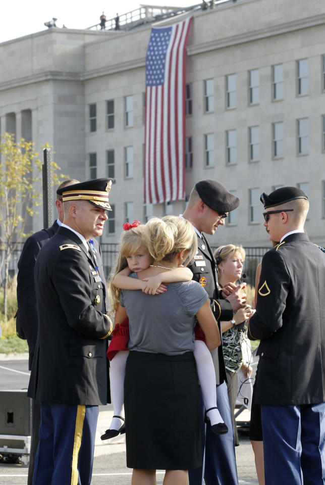 Visitors gather near a flag marking the spot where on September 11, 2001 a passenger jet was flown into the Pentagon building, during ceremonies marking the 10th anniversary of the 9/11 attack on the Pentagon, in Washington, September 11, 2011.  (REUTERS/Jason Reed)