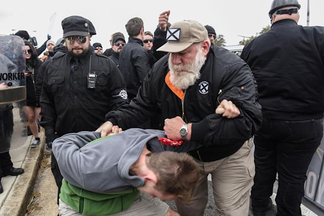 """<p>A person thought to be an infiltrator is held by people participating in a """"White Lives Matter"""" rally in Shelbyville, Tenn., Oct. 28, 2017. (Photo: Stephanie Keith/Reuters) </p>"""