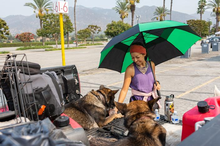 "Juanita Aldana gives her dogs water at a Red Cross temporary evacuation site at Santa Anita Park. <span class=""copyright"">(Gabriella Angotti-Jones / Los Angeles Times)</span>"