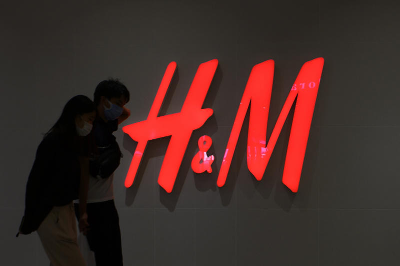 TOKYO, JAPAN - 2020/10/11: A couple wearing facemasks walks past an H&M logo and Clothing retail store in Tokyo. (Photo by James Matsumoto/SOPA Images/LightRocket via Getty Images)