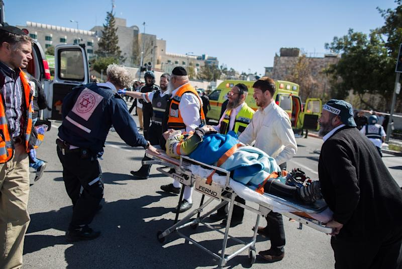Israeli police and medics carry an injured person after a car ploughed into pedestrians in Jerusalem injuring several people, before its driver got out and tried to stab them, on March 6, 2015