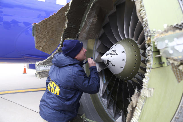<p>A National Transportation Safety Board investigator examines damage to the engine of the Southwest Airlines plane that made an emergency landing at Philadelphia International Airport in Philadelphia., Pa., on April 17, 2018. (Photo: NTSB via AP) </p>