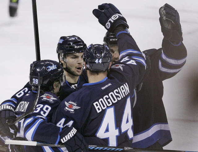 Winnipeg Jets' Tobias Enstrom (39), Michael Frolik (67), Zach Bogosian (44) and Andrew Ladd (16) celebrate Bogosian's goal against the Vancouver Canucks during the first period of an NHL hockey game in Winnipeg, Manitoba, on Friday, Jan. 31, 2014. (AP Photo/The Canadian Press, John Woods)