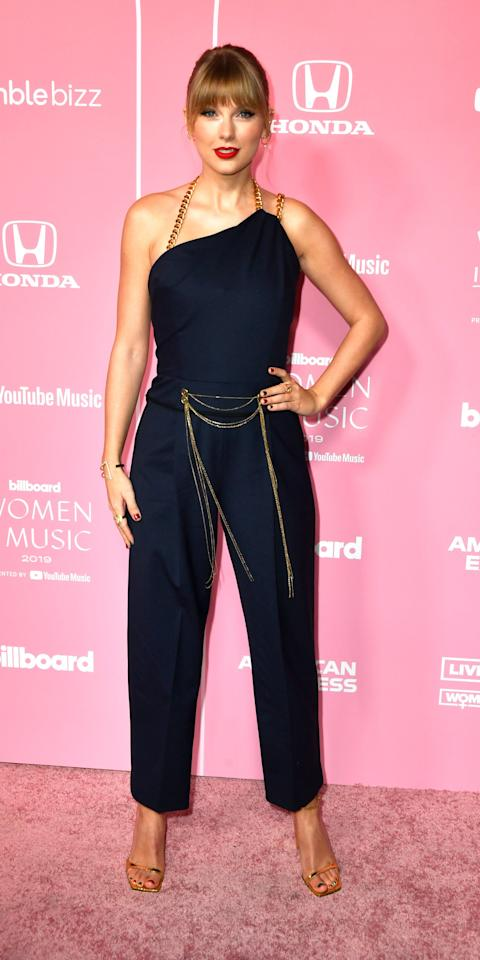 """<p>During the Billboard Women in Music event, Taylor Swift stunned in a gold chain-embellished Oscar de la Renta jumpsuit ($2,990; <a href=""""https://click.linksynergy.com/deeplink?id=93xLBvPhAeE&mid=24449&murl=https%3A%2F%2Fwww.net-a-porter.com%2Fus%2Fen%2Fproduct%2F1201207&u1=IS%2CTaylorSwift%2Canesta%2C%2CIMA%2C3506822%2C201912%2CI"""" target=""""_blank"""">net-a-porter.com</a>), Âme ear cuffs, and Marli and Maxior rings.</p>"""