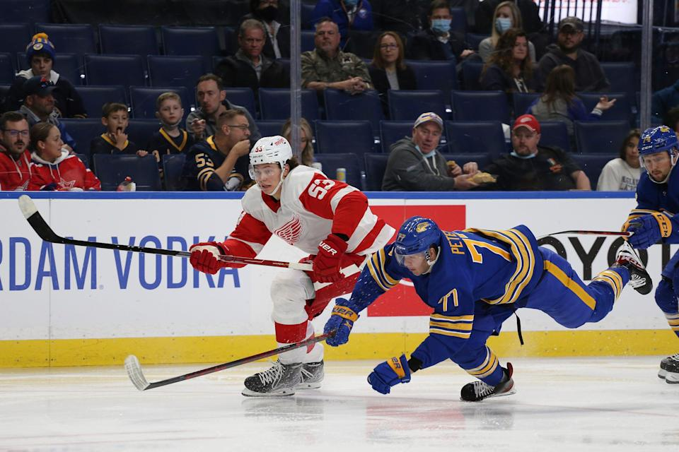 Sabres right wing John-Jason Peterka falls while battling for the puck with Red Wings defenseman Moritz Seider during the second period of the preseason game in Buffalo, N.Y., Saturday, Oct. 9, 2021.