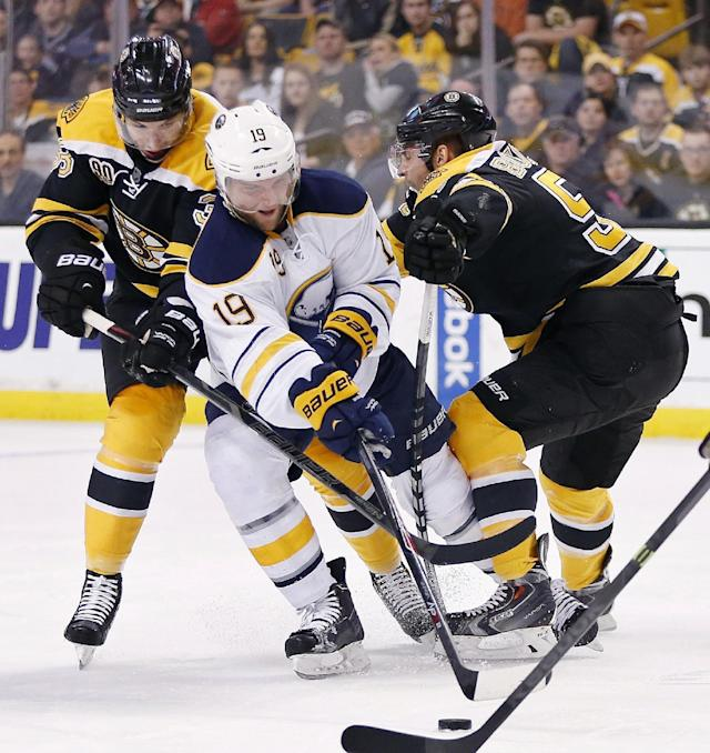 Buffalo Sabres' Cody Hodgson (19) battles Boston Bruins' Jordan Caron (38) and Johnny Boychuk (55) for the puck during the first period of an NHL hockey game in Boston, Saturday, April 12, 2014. (AP Photo/Michael Dwyer)