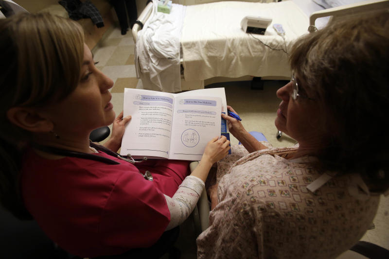 This photo taken Jan. 30, 2013 shows patient Marlena Bechtel-Rysdam, right, from Elgin, Ore., going over home monitoring training materials with registered nurse Christina Leese at Oregon Health Sciences University in Portland, Ore. Hospitals are under new pressure from Medicare to slow a pricey revolving door _ the number of people who are rehospitalized only weeks after they left for problems that could have been prevented. In Mitchell's program, patients with heart failure get extra education before they're discharged and some are tracked at home with special telemedicine monitors. (AP Photo/Don Ryan)