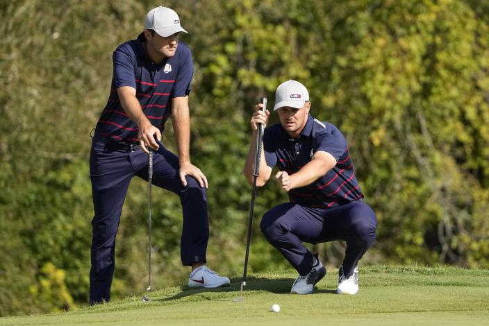 Team USA's Bryson DeChambeau and Team USA's Scottie Scheffler look over a shot on the ninth hole during a four-ball match the Ryder Cup at the Whistling Straits Golf Course Friday, Sept. 24, 2021, in Sheboygan, Wis. (AP Photo/Jeff Roberson)