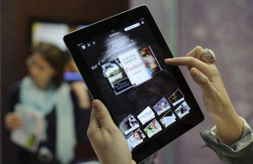 """Photo illustration of an eBook reader app on an Apple iPad. Apple on Thursday denied a charge that it schemed with publishers to hike prices for e-books, portraying itself as a hero for prying Amazon's """"monopolistic grip"""" from the market"""