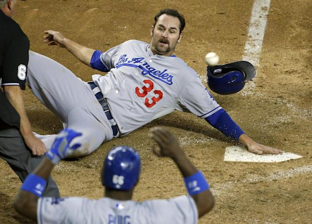 Los Angeles Dodgers' Scott Van Slyke (33) is hit with the ball as he slides in to score a run against the Arizona Diamondbacks as teammate Yasiel Puig looks on in the sixth inning of a baseball game on Thursday, Sept. 19, 2013, in Phoenix. (AP Photo/Ross D. Franklin)