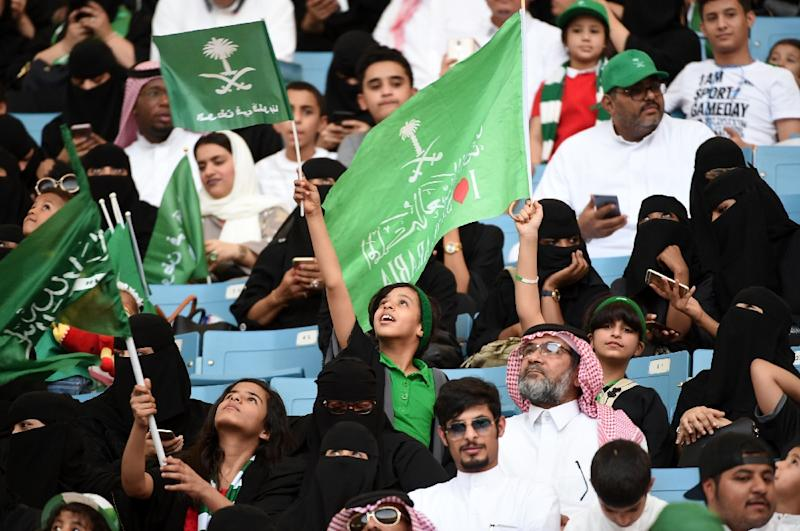 """A boy waves a flag with a caption reading in Arabic """"the nation is in our hearts"""" in a stadium in the Saudi capital Riyadh on September 23, 2017 at an event commemorating the anniversary of the kingdom's founding (AFP Photo/Fayez NURELDINE)"""