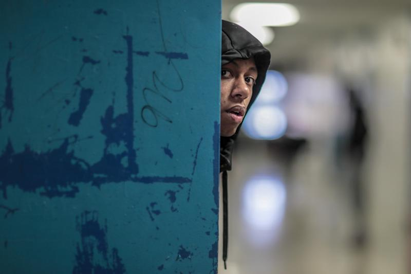 Flint's Dion Brown peers down a hallway as teammates gather before a bus takes them to a game against Davison High.