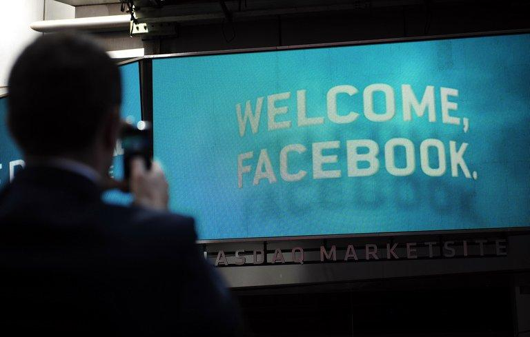 A pedestrian takes a picture a sign welcoming Facebook at the NASDAQ stock exchange in New York, on May 18, 2012