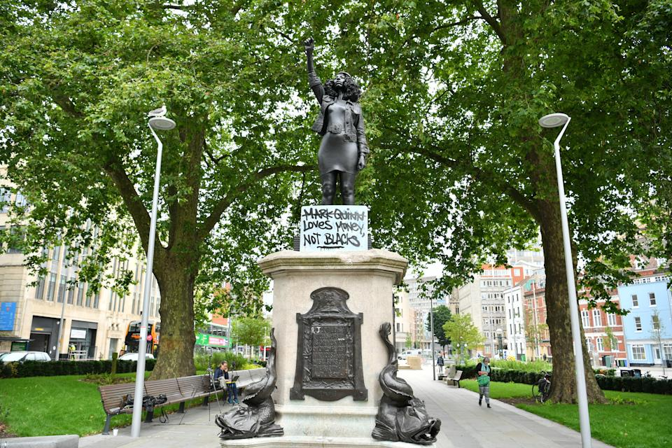 A sign is placed at the base of A Surge of Power (Jen Reid) 2020, by prominent British sculptor Marc Quinn, which has been installed in Bristol on the site of the fallen statue of the slave trader Edward Colston.