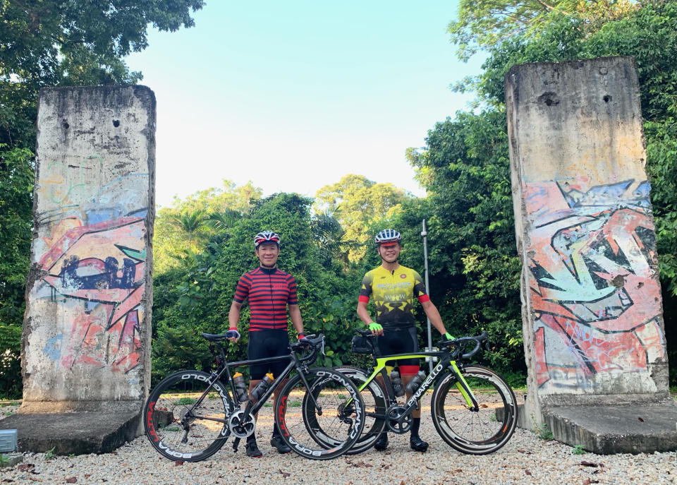 Berlin Wall Image: (from left) Dr Siong is with Bike Guru. Like many cyclists, the duo enjoys cycling to explore different parts of Singapore. They are seen here at the remnants of the Berlin Wall that divided East and West Berlin from 1961 to 1989. Located in NUS, the walls were a gift from Germany to the Singapore Ministry of Foreign Affairs in 2016, marking 50 years of diplomatic relations between Germany and Singapore. [PHOTO by Bike Guru]