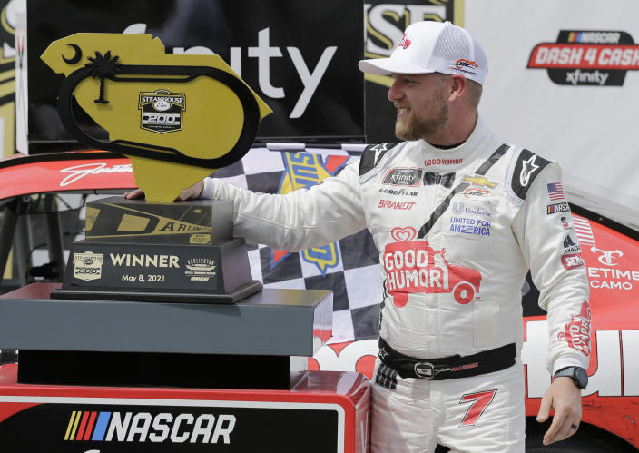 Justin Allgaier poses with the trophy in Victory Lane after winning the NASCAR Xfinity Series auto race at Darlington Raceway, Saturday, May 8, 2021, in Darlington, S.C. (AP Photo/Terry Renna)
