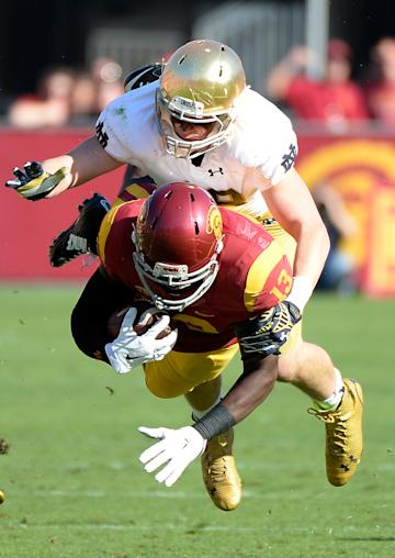 Bryce Dixon #13 of the USC Trojans is tackled by Tyler Price #49 of the Notre Dame Fighting Irish on November 29, 2014 in Los Angeles, California. (Photo by Harry How/Getty Images)
