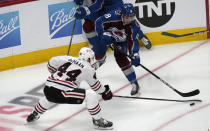 Colorado Avalanche center Alex Newhook, back, passes the puck as Chicago Blackhawks defenseman Calvin de Haan covers in the first period of an NHL hockey game Wednesday, Oct. 13, 2021, in Denver. (AP Photo/David Zalubowski)