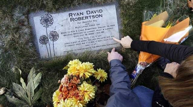 Linda and Rob Robertson point out a quote on the headstone of the grave of their son, Ryan. Photo: AP