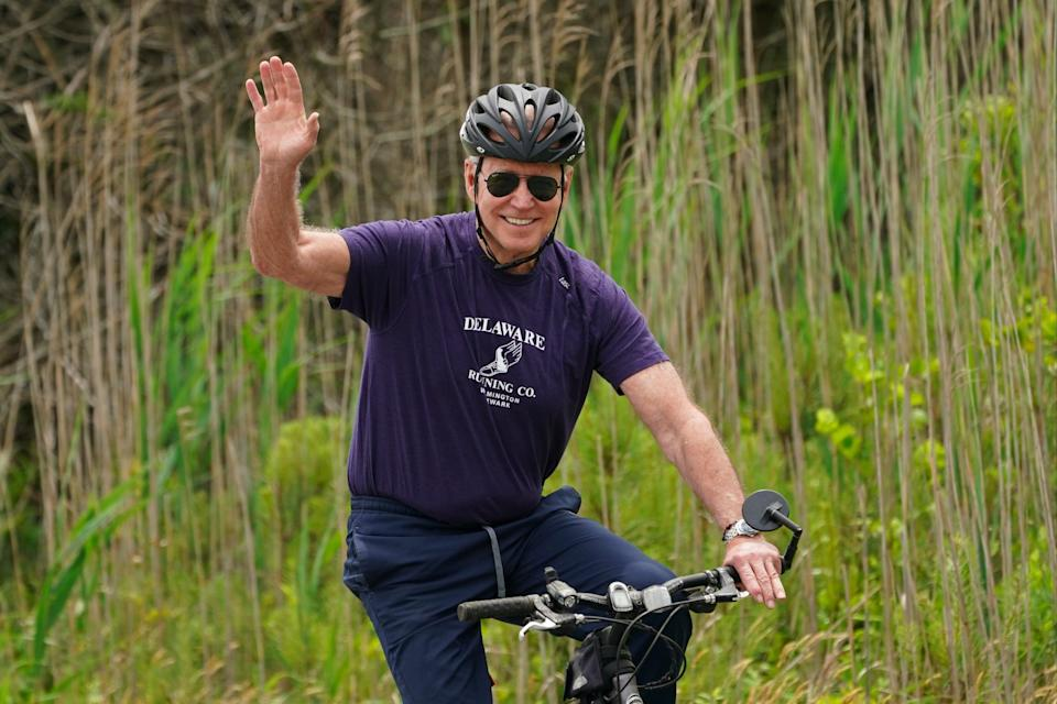 <p>Joe Biden waves from his bike while riding in Delaware</p> (REUTERS)