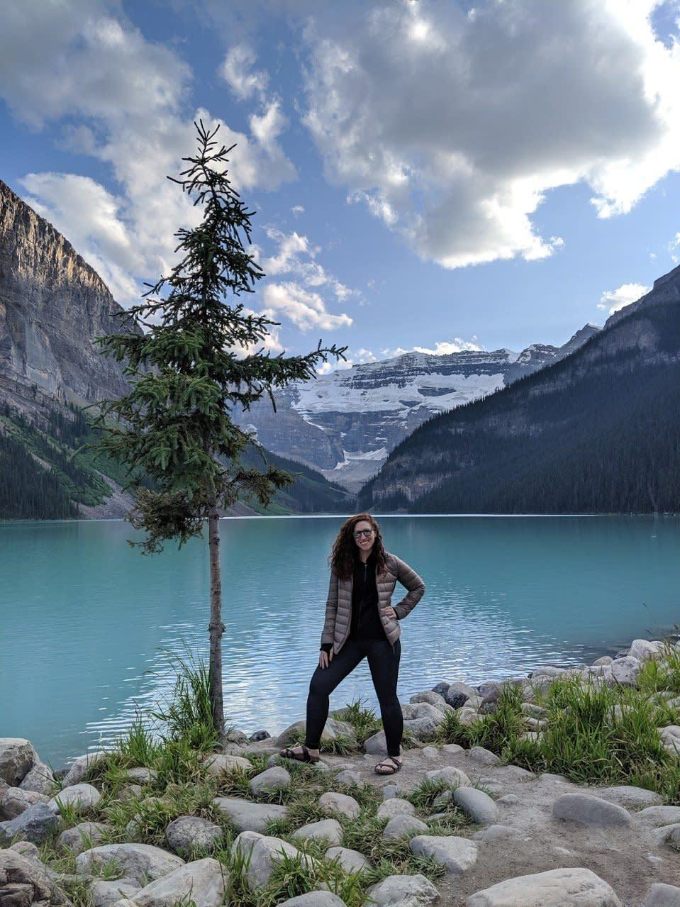 Jen standing in front of a beautiful blue lake with mountains in the background.