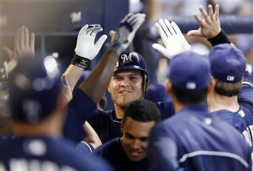 Milwaukee Brewers' Corey Hart, center, is greeted in the dugout by teammates after hitting his second solo home run off of the night off San Diego Padres' Edinson Volquez, in the fifth inning of a baseball game Friday, June 8, 2012, in Milwaukee. (AP Photo/Tom Lynn)