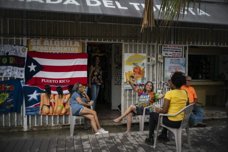 People drink beer on a patio before the arrival of Tropical Storm Dorian in Boqueron, Puerto Rico, Aug. 27, 2019. (Photo: Ramon Espinosa/AP)