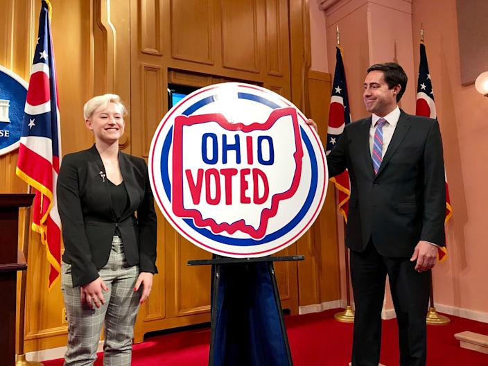 """Emily Legg of Pickaway County stands next to her winning design in Ohio Secretary of State Frank LaRose's contest seeking a new """"I voted"""" sticker on May 21, 2019 at the Ohio Statehouse."""