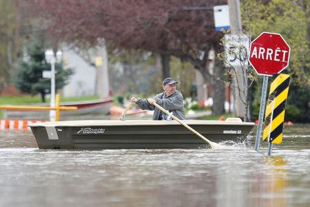 A man rows a boat on a flooded residential street in Gatineau