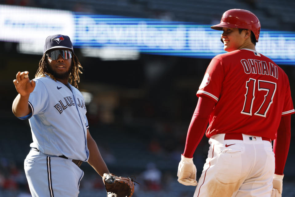 ANAHEIM, CALIFORNIA - AUGUST 10: Shohei Ohtani #17 of the Los Angeles Angels and Vladimir Guerrero Jr. #27 of the Toronto Blue Jays react while on first base during the sixth inning of game one of a doubleheader at Angel Stadium of Anaheim on August 10, 2021 in Anaheim, California. (Photo by Michael Owens/Getty Images)