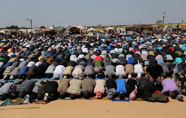 <p>Palestinians perform Friday prayers during a protest demanding the right to return to their homeland, at the Israel-Gaza border in the southern Gaza Strip, April 6, 2018. (Photo: Ibraheem Abu Mustafa/Reuters) </p>