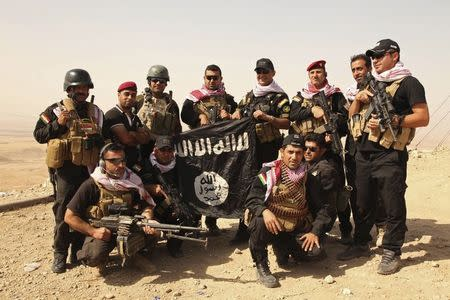 Kurdish Peshmerga fighters pose with an Islamic State flag, which they pulled down after capturing Mount Batnaya, near Zummar September 20, 2014. REUTERS/Ari Jalal