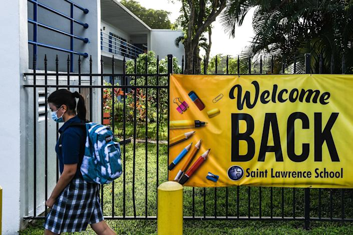 A student wears a mask as she enters the St. Lawrence Catholic School on the first day of school after summer vacation in north of Miami, on August 18, 2021.
