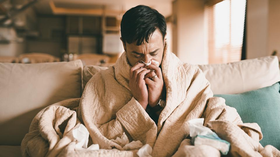 Cropped shot of a young man suffering with flu while sitting wrapped in a blanket on the sofa at home.