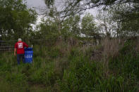 Migrant rights activist Eduardo Canales checks one of his blue water drops Saturday, May 15, 2021, in Falfurrias, Texas. Every week, Canales fills up blue water drums that are spread throughout a vast valley of Texas ranchlands and brush. They are there for migrants who venture into the rough terrain to avoid being caught and sent back to Mexico. (AP Photo/Gregory Bull)