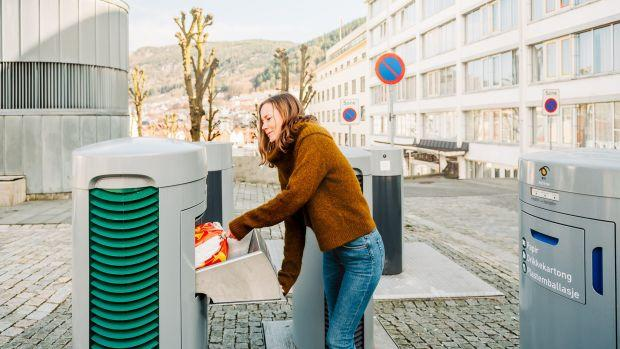 A woman places a small red and white bag of trash inside of a squat gray metal box built into the cobblestone streets of Bergen, Norway.
