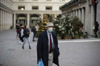 A man wearing a face mask walks backdropped by Christmas trees in Covent Garden, during England's second coronavirus lockdown in London, Thursday, Nov. 26, 2020. As Christmas approaches, most people in England will continue to face tight restrictions on socializing and business after a nationwide lockdown ends next week, the government announced Thursday. (AP Photo/Matt Dunham)