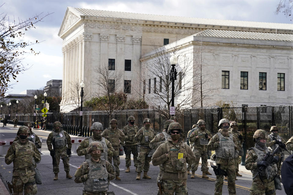 Members of the National Guard stand at a road block near the Supreme Court ahead of President-elect Joe Biden's inauguration ceremony, Wednesday, Jan. 20, 2021, in Washington. (AP Photo/John Minchillo)