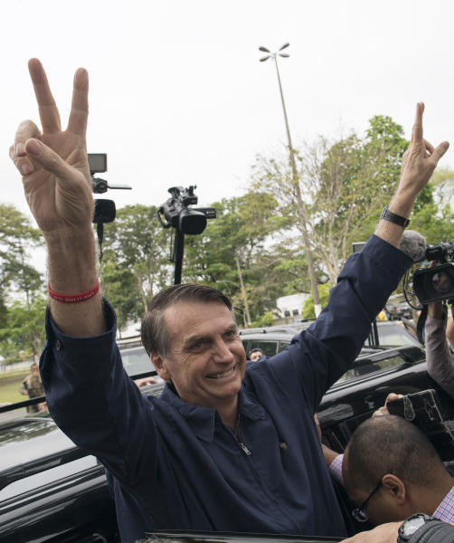 In this Sunday, Oct. 7, 2018 photo, presidential frontrunner Jair Bolsonaro flashes victory hand signs to supporters after voting at a polling station in Rio de Janeiro, Brazil. Bolsonaro just missed outright victory in Sunday's vote, and will face former Sao Paulo Mayor Fernando Haddad of the leftist Workers' Party in an Oct. 28 runoff. (AP Photo/Leo Correa)