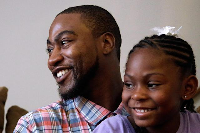 Adrian Arrington, a former safety at Eastern Illinois University, sits with his daughter, Andria, as he talks about enduring five concussions while playing football, some so severe he has says he couldn't recognize his parents afterward, during an interview with The Associated Press at his home Tuesday, July 29, 2014, in Bloomington Ill. Subsequent headaches, memory loss, seizures and depression made it difficult to work or even care for his children. On Tuesday, the NCAA agreed to settle a class-action head-injury lawsuit by creating a $70 million fund to diagnose thousands of current and former college athletes to determine if they suffered brain trauma playing football, hockey, soccer and other contact sports. Arrington was the lead plaintiff in the lawsuit. (AP Photo/Seth Perlman)