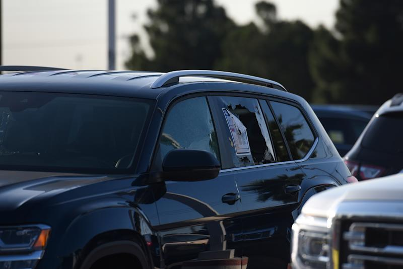 A vehicle with a broken window is seen as Texas state troopers and other emergency personnel monitor the scene at a local car dealership following a shooting in Odessa, Texas, U.S. September 1, 2019. REUTERS/Callaghan O'Hare